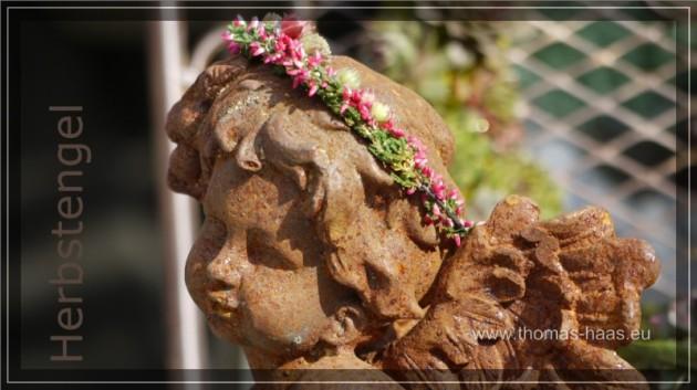 Eine Rostbraune Engelsskulptur mit Blumenkranz