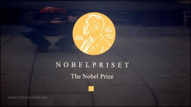 Spiegelung in einer mit dem Nobelpreislogo beklebten Nobelkarosse.