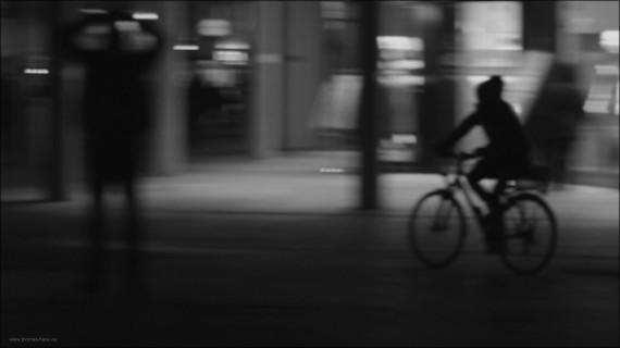 Eine Radfahrerin sucht den Weg über den nächtlichen Münsterplatz, Jan. 2015