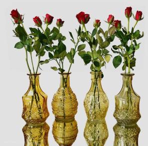 Vasen mit Rosen auf Spiegelplatte