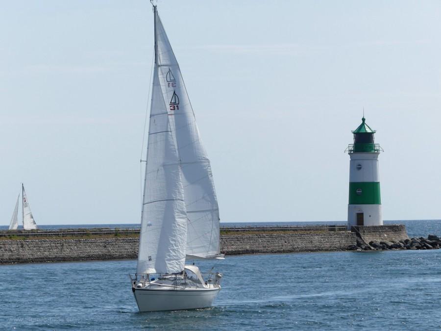 Segelboot und die Mole mit dem Leuchtturm in Schleimünde, Ostsee